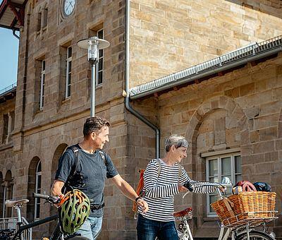 Zwei Personen stehen mit ihren Rädern vor dem Bahnohsgebäude von Hasbergen