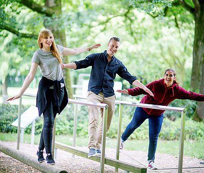 Drei Personen an einer Sinnenstation im Kurpark von Bad Laer