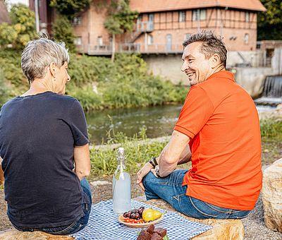 Zwei Personen machen eine Picknickpause an einem Fluss